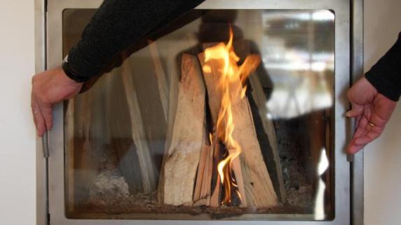 Effizient heizen: Zu viel Holz im Ofen: Ruß lagert sich auf Glasscheibe ab