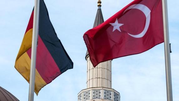 Die deutsche und die türkische Fahne vor einer Moschee