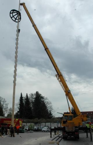 Mit Hilfe eines Autokrans wird der Maibaum aufgestellt (Bild links). Für zwei Jahre schmückt der Maibaum den Schwabmünchner Schrannenplatz (Bild rechts).