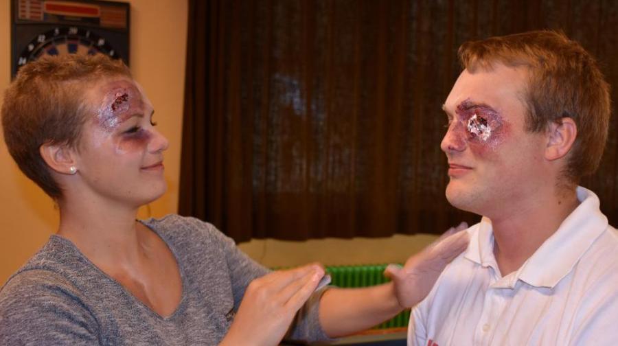 Freiwillige der Johanniter-Unfall-Hilfe (Bild links) schminken sich gegenseitig als schwer verletzte Opfer des Busunfalls.